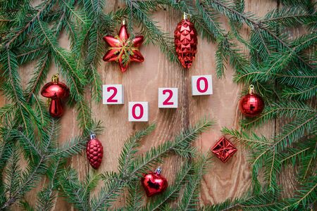 Christmas wooden background with fir branches and red toys by 2020 Stok Fotoğraf