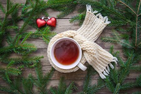 Cozy picture with a mug of tea in a scarf, Christmas tree branches and red hearts on a rustic wooden background 스톡 콘텐츠