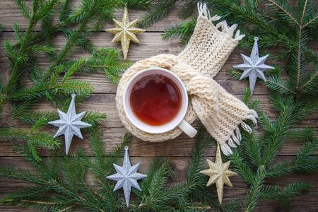 Cozy picture with a mug of tea in a scarf, Christmas tree branches and five stars on a rustic wooden background