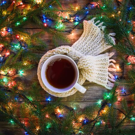 Cozy evening winter Christmas picture with a mug of hot tea in a knitted scarf surrounded by colorful lights garlands Zdjęcie Seryjne - 133357048