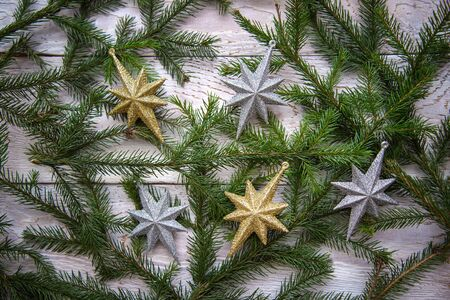 Christmas tree branches and stars on a white wooden background