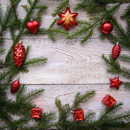 Frame from Christmas tree branches and red ornaments on a light wooden background, copy space