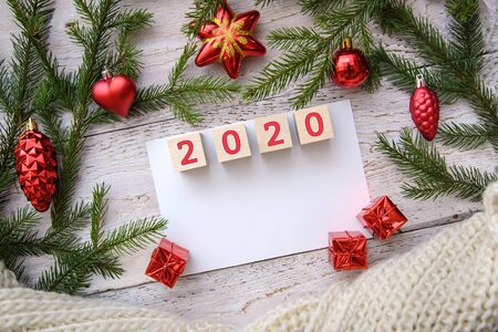 2020 year in a frame of Christmas tree branches and red toys on a wooden background, greeting card design, copy space
