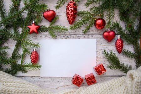 Frame of Christmas tree branches and red toys on a wooden background, greeting card design, copy space 스톡 콘텐츠