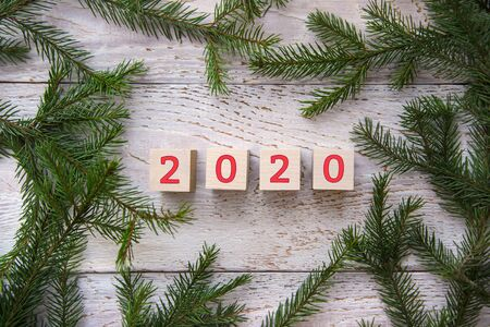 2020 in a frame of green Christmas tree branches on a white wooden background Stok Fotoğraf