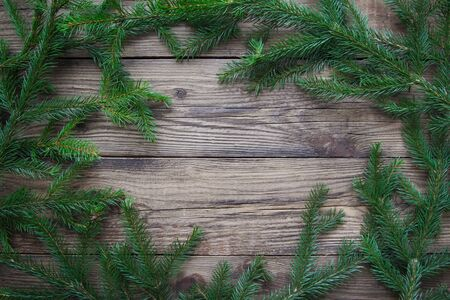 Frame of green Christmas tree branches on rustic wooden background with copy space 스톡 콘텐츠