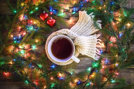 Cozy evening winter Christmas picture with a mug of hot tea in a knitted scarf surrounded by colorful lights garlands