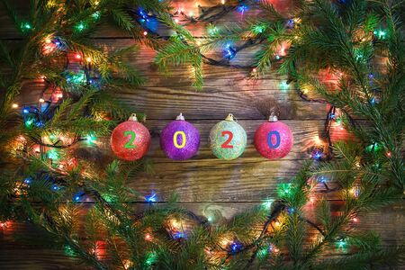 Cozy winter picture with Christmas tree branches, colorful lights and balls with 2020 on a wooden background