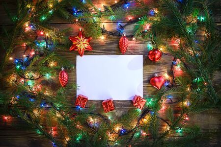 Cozy picture with Christmas tree branches, colorful lights, toys and a sheet of paper on a wooden background, with copy space