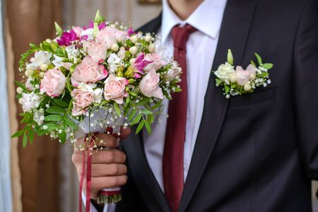 Wedding bouquet of pink roses in the hands of the groom in a black suit closeup