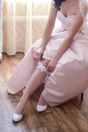 A bride in a beige dress wears a white lace wedding garter on her leg in the morning in the room