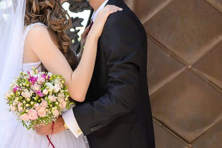 The groom gently embraces the bride in a white dress with a wedding bouquet close up Stock fotó