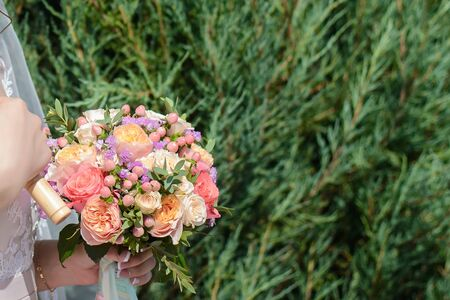 Beautiful wedding bouquet of white and pink flowers in the hands of the bride on the background of green foliage close up with a copy of the space Stock fotó