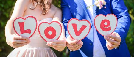 The word LOVE on wooden white boards in the shape of a heart in the hands of the bride and groom close up