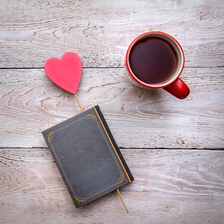 Square romantic photo with a mug of tea and a book with a heart on a rustic wooden background, for Valentine's day