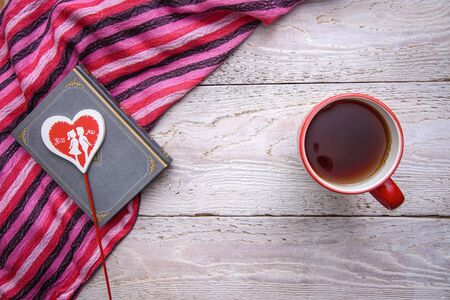 Horizontal romantic photo with a mug of tea and a book with a heart on a rustic wooden background, for Valentines day Фото со стока