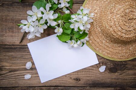 A branch of a blooming apple tree with white flowers, sheet of paper and a straw hat on a rustic wooden background, with a copy space, top view
