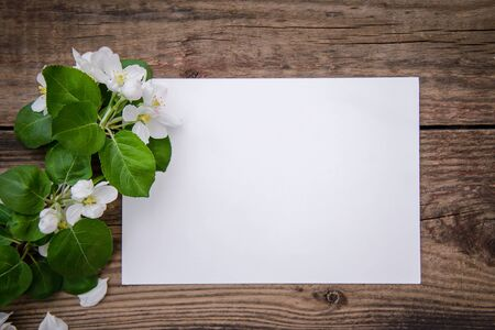A branch of a blooming apple tree with white flowers and a sheet of paper on a rustic wooden background, with a copy space, top view