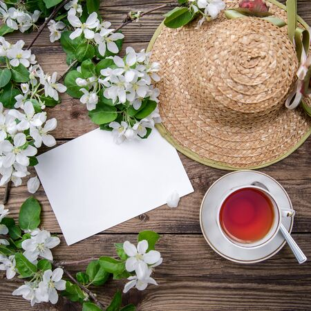 Spring layout with branches of a blooming apple tree in white flowers, a cup of fragrant tea and a straw hat on a rustic wooden background, top view Фото со стока