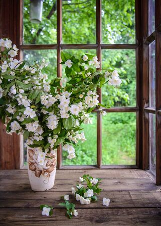 A large beautiful bouquet of Jasmine branches in a vase by a wooden window in the countryside