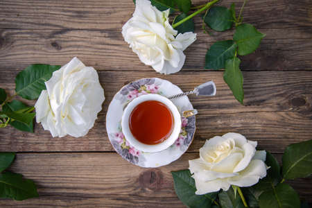 Three beautiful white roses and a cup of tea on a rustic wooden background