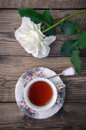 A beautiful white rose and a cup of tea on a rustic wooden background