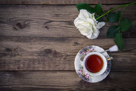 A beautiful white rose and a cup of tea on a rustic wooden background, copy space