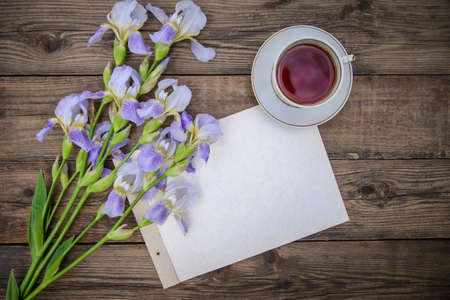 Beautiful purple flowers irises, a sheet of paper and a cup of tea on a wooden rustic background in summer, top view, with copy space Reklamní fotografie
