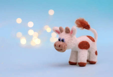 Symbol of 2021, a toy felt bull or cow on a festive light blue background with bokeh, with a copy space Standard-Bild