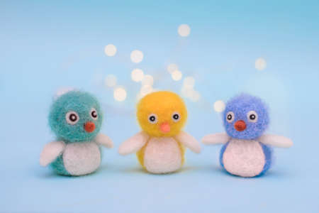 Three small felt colorful cute fluffy birds on a light blue background with bokeh
