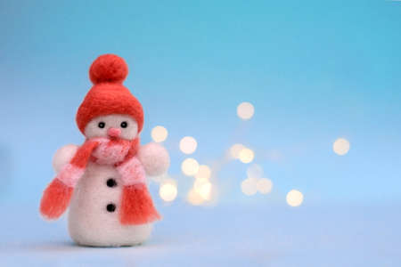 Christmas toy felted wool snowman in a red winter hat on a blue background with bokeh, copy space Standard-Bild