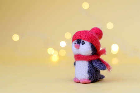 Christmas toy felted wool cute little penguin in a winter red hat and scarf on a yellow background with bokeh, copy space