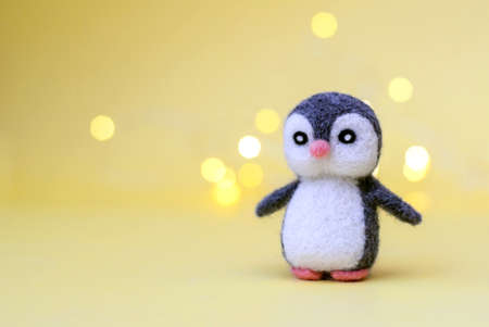 Christmas toy felted wool cute little penguin on a yellow background with bokeh, copy space