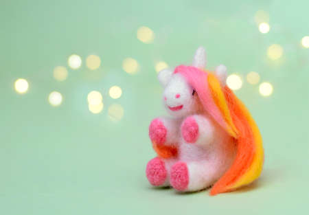 Toy felted wool cute little unicorn with long multi-colored mane on a green background with bokeh, copy space