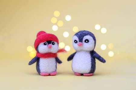 Two Christmas toy felted wool cute little penguins on a yellow background with bokeh Stock Photo