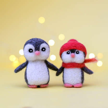 Two Christmas toy felted wool cute little penguins on a yellow background with bokeh Standard-Bild