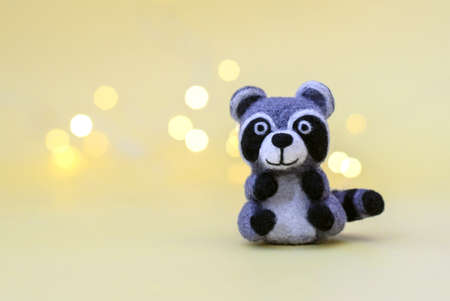 Christmas toy felted wool cute little raccoon on a yellow background with bokeh, copy space