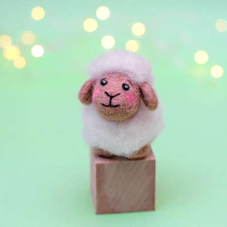 Toy felted wool cute little lamb on a green background with bokeh, copy space