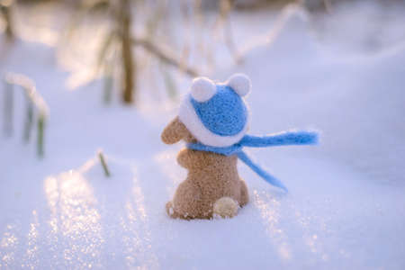 Toy wool felted cute rabbit, hare in a blue hat and scarf stands in the snow from the back on a sunny winter day