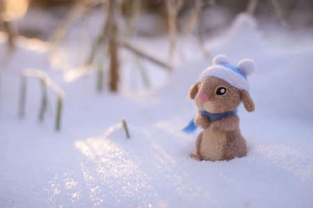 Toy wool felted cute rabbit, hare in a blue hat and scarf stands in the snow on a sunny winter day