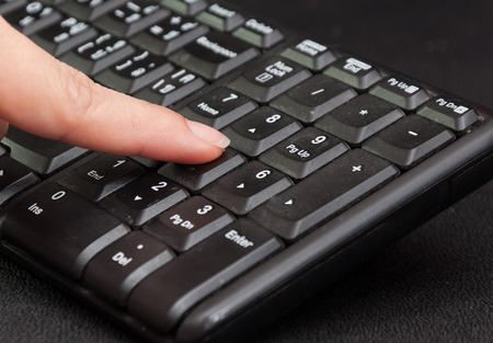 Female finger typing on computer number keyboard photo