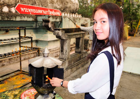 Asian girl light a candle at temple photo