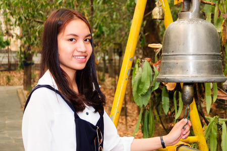 Asian girl ring the bell at temple photo