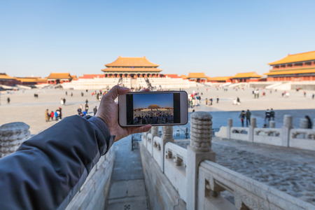 Taking photos with a mobile phone in the Forbidden City in Beijing