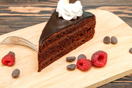 Chocolate cake with chocolate cream and icing. Fresh raspberries and coffee Stock Photo