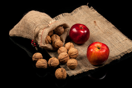 Whole nuts and apples on a table on a black background