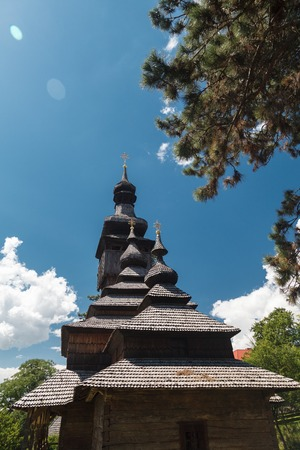 rooftile: Old wooden Lemk church against a bright blue sky with clouds.