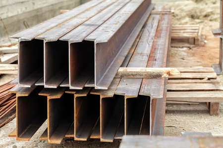 Metal beams lie on a wooden pallet. Outdoors Stock Photo