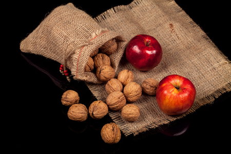 Whole nuts with fresh red apples on a table on a black background