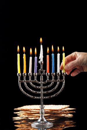 Menorah with candles for Hanukkah on black background Stock Photo